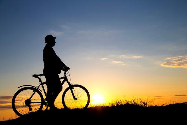 Schattenbild der sportperson, die auf dem feld auf dem schönen sonnenuntergang radelt