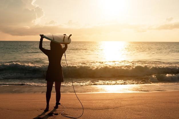 Schattenbild der surferfrau, die ihre surfbretter am sonnenuntergangsstrand mit sonnenlicht trägt