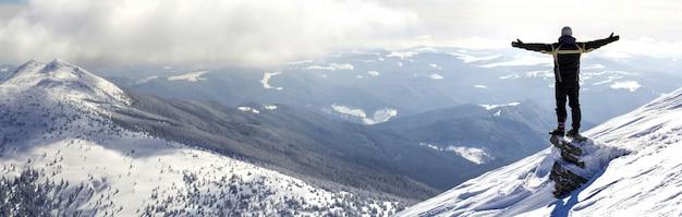 Schattenbild des allein stehenden touristen, der auf schneebedecktem berggipfel steht