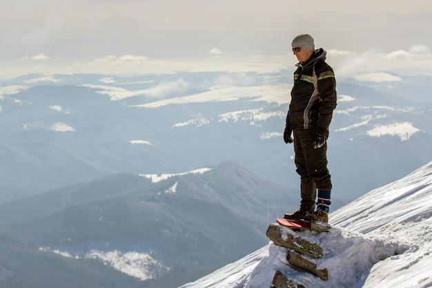 Schattenbild des allein stehenden touristen, der auf schneebedeckter bergspitze steht, die ansicht und leistung am hellen sonnigen wintertag genießt.