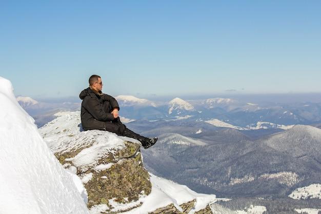 Schattenbild des alleinigen touristen, der auf schneebedeckter bergspitze sitzt, die ansicht und leistung am hellen sonnigen wintertag genießt. abenteuer, aktivitäten im freien, gesunder lebensstil.