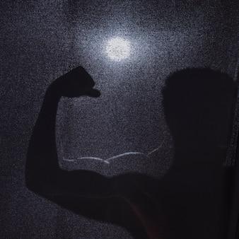 Schattenbild des anonymen mannes, der muskeln biegt