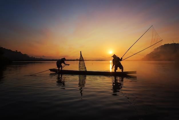 Schattenbild des asiatischen fischers auf hölzernem boot