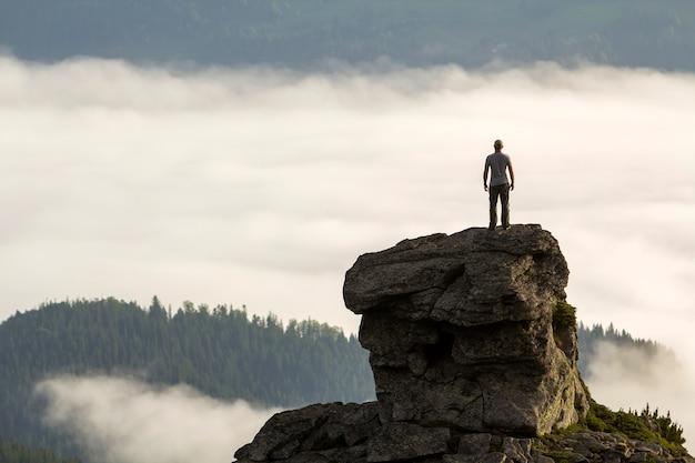Schattenbild des athletischen bergsteigertouristen auf hoher felsiger bildung auf gebirgstal füllte mit weißen geschwollenen wolken.