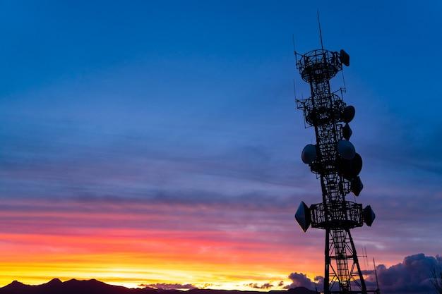 Schattenbild des beweglichen telekommunikations-signal-masts, radioantennen turm über bunten sonnen