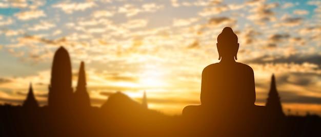 Schattenbild des buddha auf goldenem tempelsonnenuntergang. reiseattraktion in thailand.