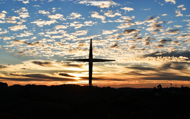 Schattenbild des christlichen kreuzes und der windkraftanlagen bei sonnenuntergang