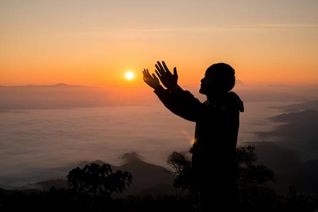 Schattenbild des christlichen mannes, der bei sonnenuntergang betet