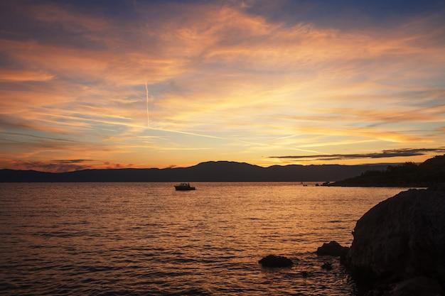 Schattenbild des einsamen bootes im sonnenuntergang mit dramatischem himmel. sonnenuntergang auf hoher see mit einem fischereifahrzeug am horizont.