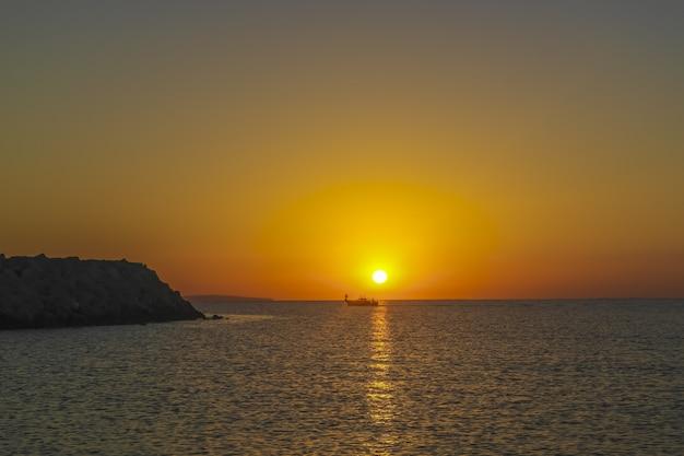 Schattenbild des fischerbootes auf dem meer bei schönem sonnenaufgang