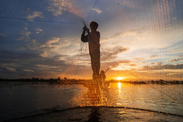 Schattenbild des fischers auf fischerboot mit netz auf dem see bei sonnenuntergang, thailand
