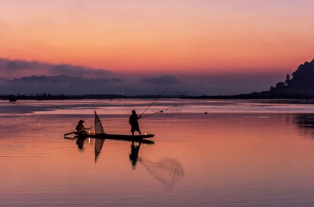 Schattenbild des fischers auf hölzernem boot im natursee mit sonnenaufgang