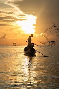 Schattenbild des fischers auf seinem boot bei sonnenaufgang morgens.