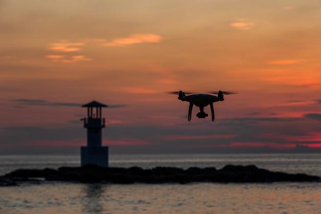 Schattenbild des fliegenbrummens, das foto über sonnenuntergangmeer macht