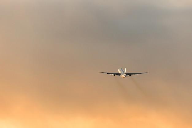 Schattenbild des flugzeugs, das während eines dramatischen sonnenuntergangshimmels abhebt, kopieren raum. luftfahrt.