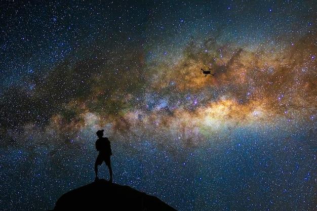 Schattenbild des fotografen mit brummen über der milchstraße auf dem bewölkten himmel