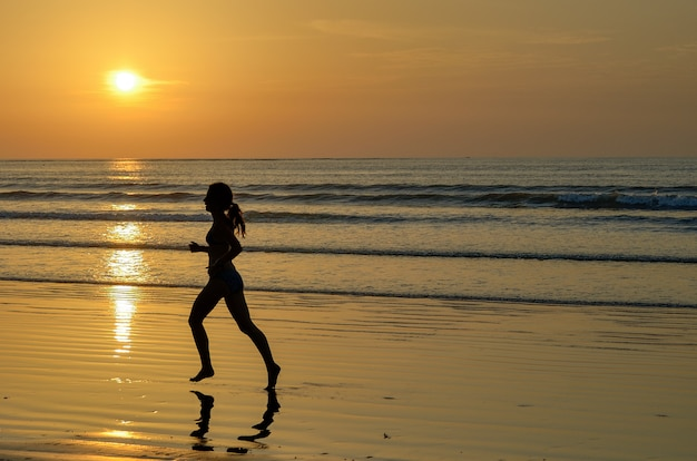 Schattenbild des frauenjoggers, der auf sonnenuntergangsstrand, fitness und gesundes lebenskonzept läuft