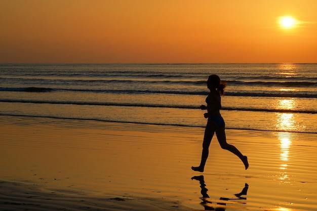 Schattenbild des frauenrüttlers laufend auf sonnenuntergangstrand mit reflexions-, eignungs- und sportkonzept
