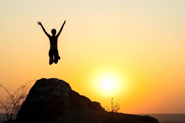 Schattenbild des frauenwanderers, der allein auf leerem felsen bei sonnenuntergang in den bergen springt. weibliche touristin, die ihre hände auf stehend auf klippe in der abendnatur erhebt.