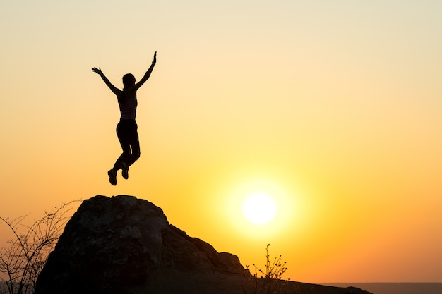 Schattenbild des frauenwanderers, der allein auf leerem felsen bei sonnenuntergang in den bergen springt. weiblicher tourist, der ihre hände auf stehend auf klippe in der abendnatur erhebt. konzept für tourismus, reisen und gesunden lebensstil.
