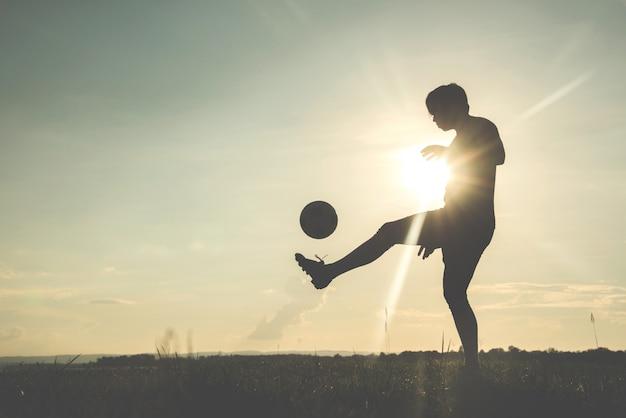 Schattenbild des fußballspielers mit einem soccerball gegen den sonnenunterganghintergrund.