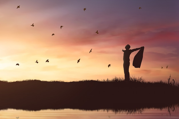 Schattenbild des geschäftsmannes die sonne genießend, die mit fliegenvögeln scheint