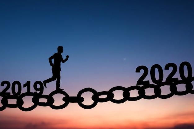 Schattenbild des geschäftsmannes gehend und auf kettenbrücke von 2019 bis 2020 laufend