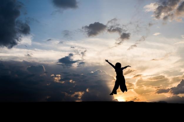Schattenbild des glücklichen frauenspringens und -sonnenuntergangs