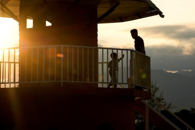 Schattenbild des glücklichen kleinen jungen und des mannes auf balkon im haus mit sonnenaufflackern