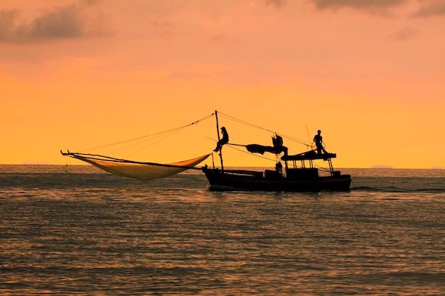 Schattenbild des heimischen fischereiboots in thailand gegen schönen sonnenuntergangshimmel