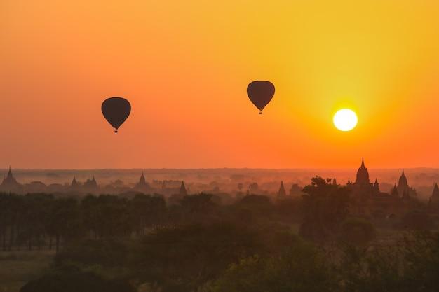 Schattenbild des heißluftballons über bagan bei sonnenaufgang im nebligen morgen, myanmar