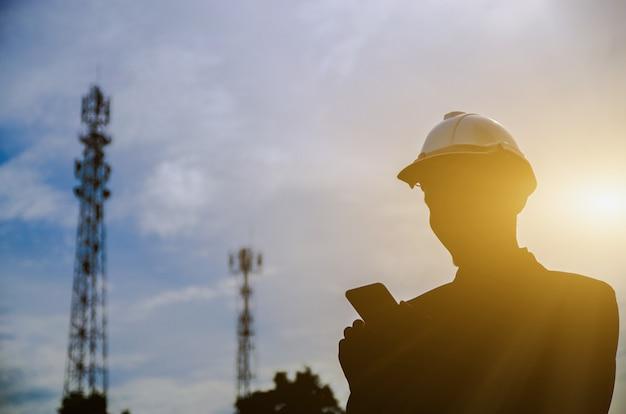 Schattenbild des ingenieurs, der ein handy mit telekommunikationsantenne und sonnenunterganghintergrund hält.