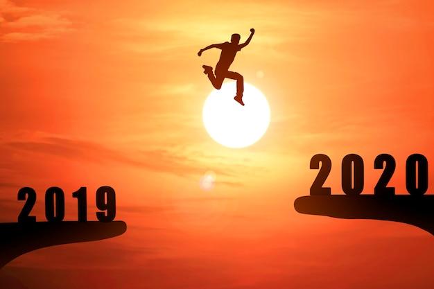 Schattenbild des jungen geschäftsmannes springend von 2019 bis 2020