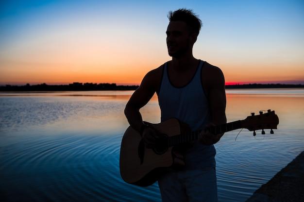 Schattenbild des jungen gutaussehenden mannes, der gitarre am meer während des sonnenaufgangs spielt
