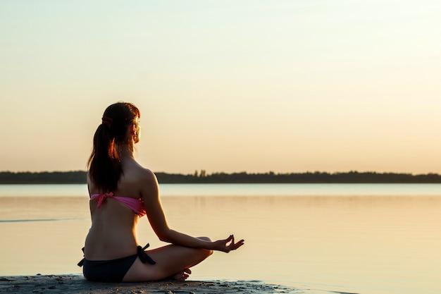 Schattenbild des jungen mädchens, yoga auf natur, auf von einem see und von einem schönen sonnenuntergang