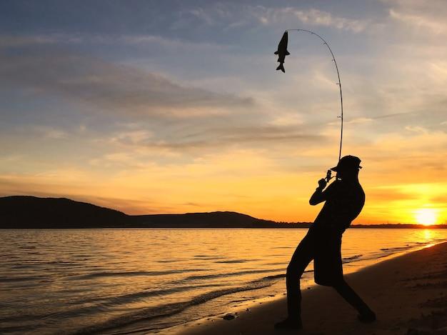 Schattenbild des jungen mannes, der durch den see bei sonnenuntergang fischt