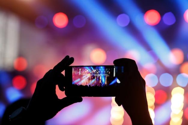 Schattenbild des jungen mannes, der fotorockkonzert auf dem handy, fest im freien nimmt