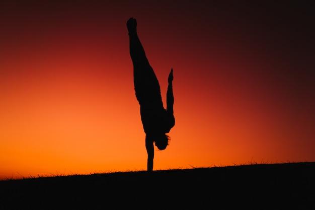 Schattenbild des jungen mannes in einem park, der yoga tut