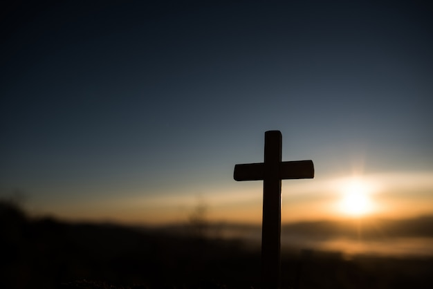 Schattenbild des katholischen kreuzes und des sonnenaufgangs