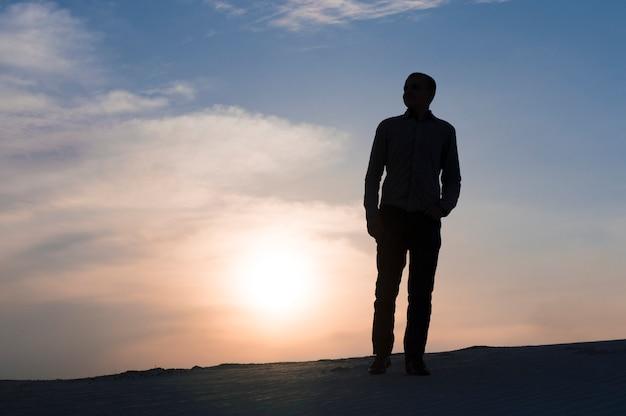 Schattenbild des kerls zur sonnenuntergangszeit am himmel