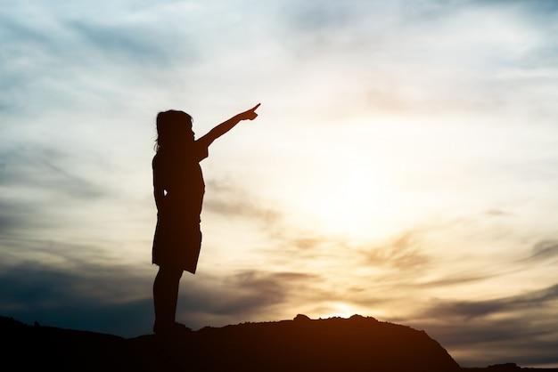 Schattenbild des kleinen mädchens hand zur glücklichen zeit der freiheit anhebend