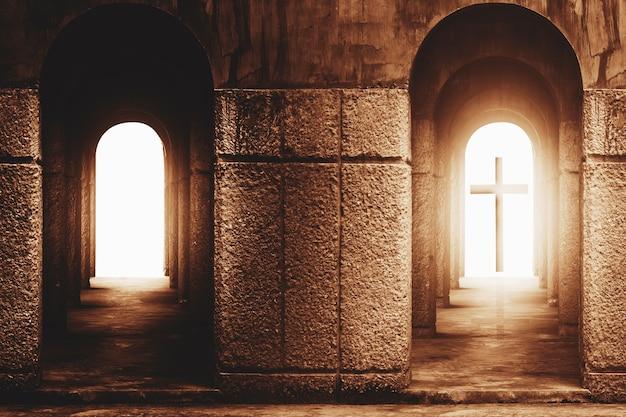 Schattenbild des kreuzes am ende des tunnels mit strahl des sonnenlichts hinten