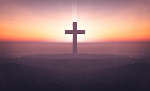 Schattenbild des kruzifixkreuzes auf berg zur sonnenuntergangzeit mit heiligem und hellem hintergrund.