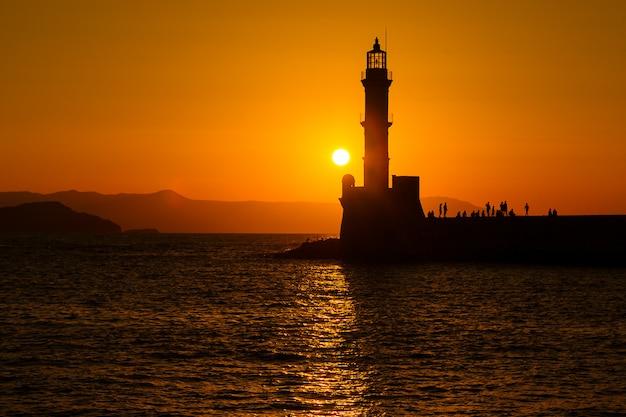 Schattenbild des leuchtturmes im meer bei sonnenuntergang in der stadt von chania, insel von kreta, griechenland. schöner meerblick bei sonnenuntergang