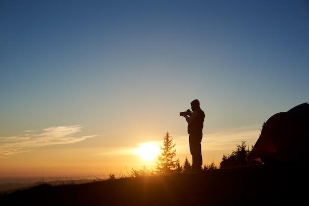 Schattenbild des männlichen fotografen mit fotokamera bei sonnenaufgang