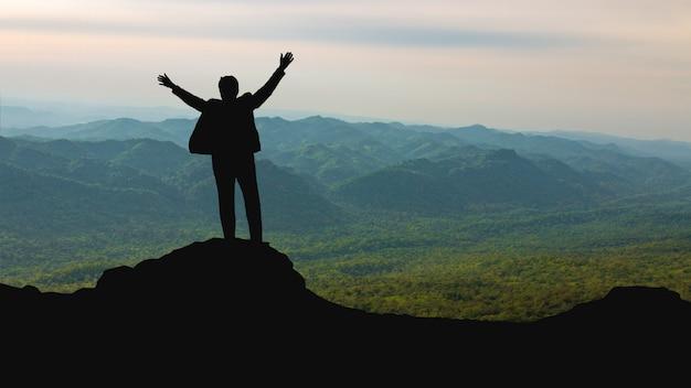 Schattenbild des mannes auf die gebirgsoberseite über hellem erfolg des himmels und der sonne, führung und leutekonzept