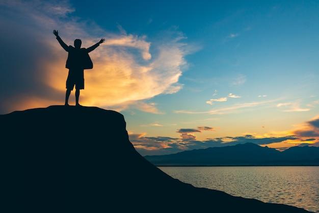 Schattenbild des mannes auf die gebirgsoberseite über hellem hintergrund des himmels und der sonne