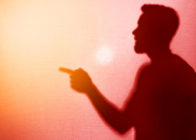 Schattenbild des mannes beiseite zeigend