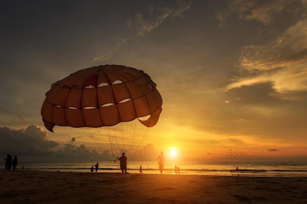 Schattenbild des mannes bereitet para-segeln am sonnenuntergangstrand in thailand vor