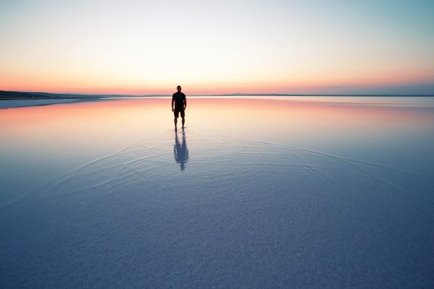 Schattenbild des mannes, der in sonnenuntergang auf glattem wasser des sees abreist
